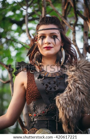 The dark-haired warrior in armor Amazon in forrest - stock photo
