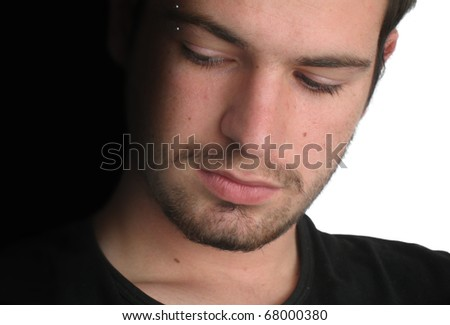 The dark side: closeup of a young man looking towards the dark side - stock photo