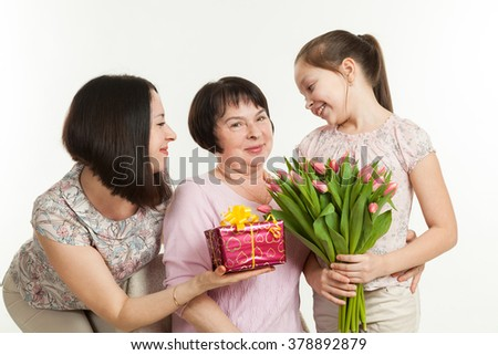 the daughter and the granddaughter give a bouquet of tulips to the grandmother - stock photo