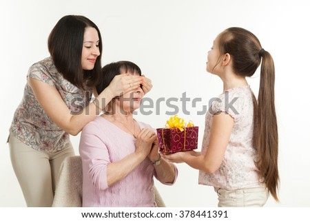 the daughter and the granddaughter give a gift to the grandmother