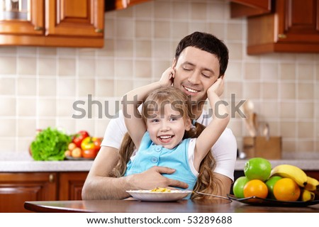 The daughter embraces the daddy on kitchen - stock photo