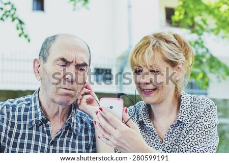 The daughter shows old father technology  - stock photo