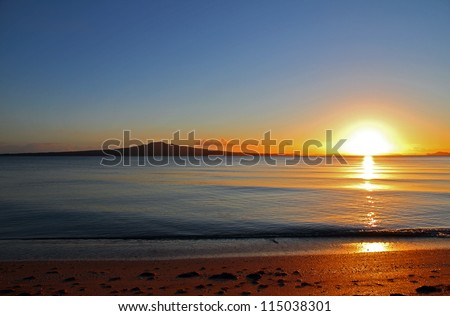 The dawn of a new day as the sun rises beside Rangitoto Island, Auckland, New Zealand - stock photo
