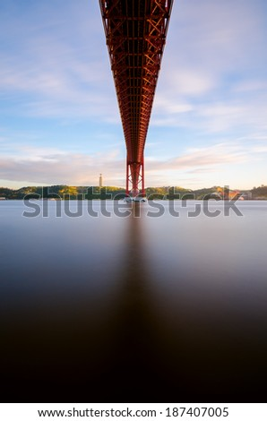 The 25 de Abril bridge over Tagus river and big Christ monument in Lisbon at sunset, Portugal - stock photo