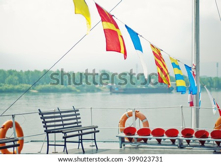 The deck of the ship with a bench and waving colorful flags on the background of the river in a light haze