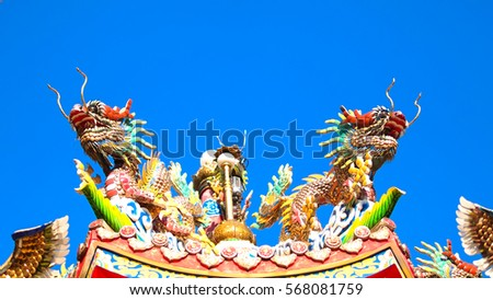 The decoration of dragons and bird on the Chinese shrine roof with the blue sky.