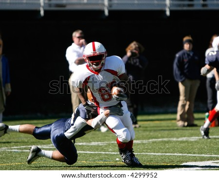 The defensive desperately tries to dive after the receiver, who slips free for a long touchdown run. - stock photo