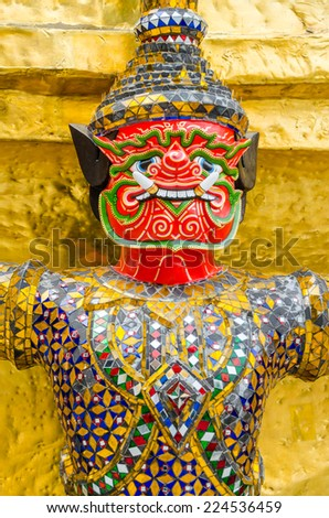 The demon statue supporting golden pagoda in the temple of the Emerald Buddha (Wat Phra Kaew) , Bangkok, Thailand.