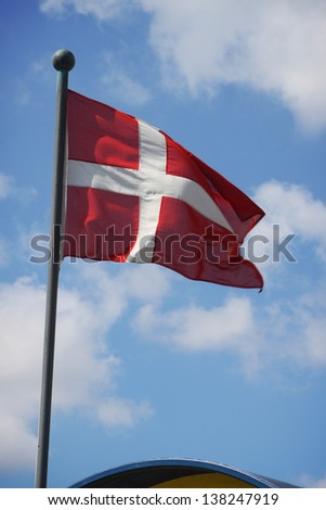 The Denmark flag waving on the wind against blue sky with white clouds - stock photo