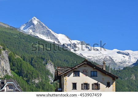 The Dent Blanche in the southern swiss alps, with surrounding glaciers and some traditional local houses in the foreground - stock photo