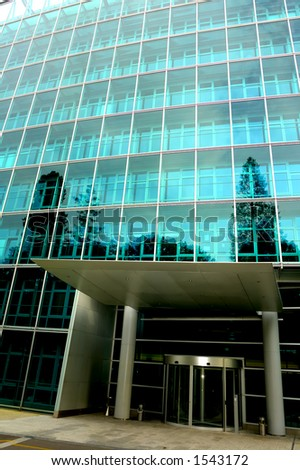 The deserted front door of an office block, trees reflected in the glass. One tree reflection appears to grow out of a pillar. Contrast between light at top of building and dark below. - stock photo