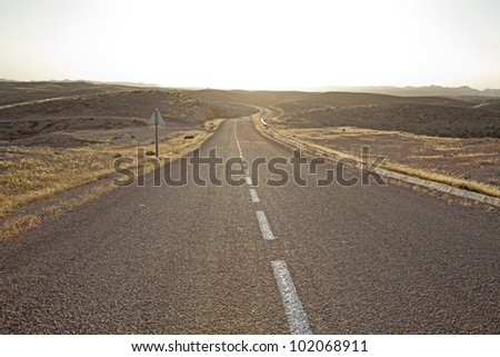 The desolated desert highway with a sharp bend at the end. - stock photo