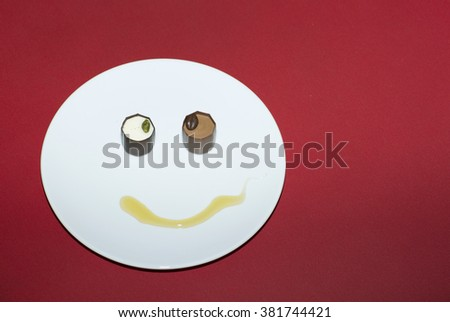 The dessert, chocolate and honey. Smiley with candy and honey on the plate.