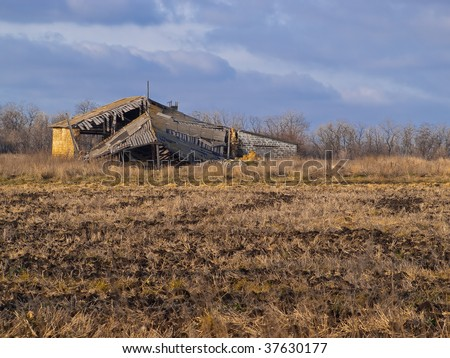 The destroyed house in the middle of a dark autumn field - stock photo