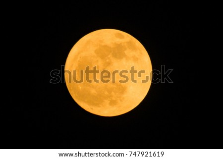 the detail of yellow full moon on black background , zoom image