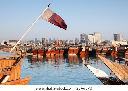 The dhow harbour in Doha, Qatar, with the national flag. - stock photo
