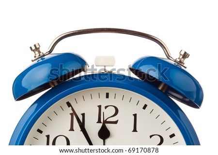 The dial of an alarm clock shows five before 12