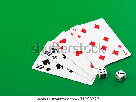 The dice and playing cards on green background.