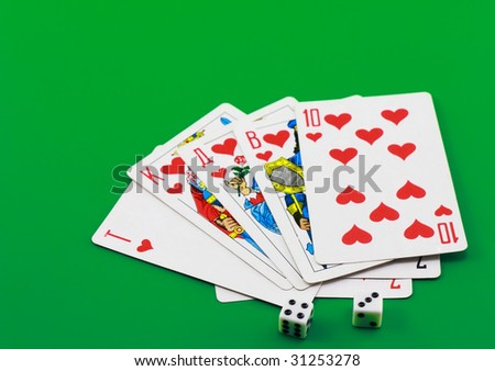 The dice and playing cards on green background. - stock photo