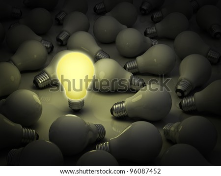 The different in business concept, one lit light bulb standing out from the unlit incandescent bulbs - stock photo