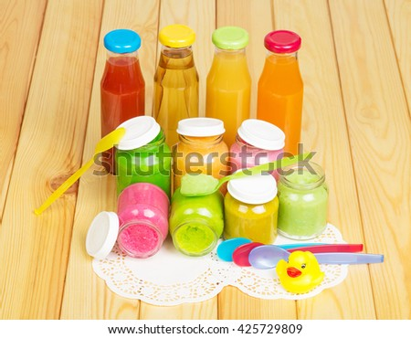 The different juices in bottles, jars of baby puree, colored spoons and rubber duck on a background of light wood.