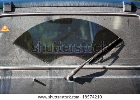 The dirty back window of an automobile - stock photo