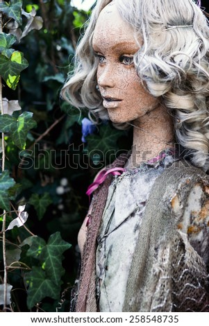The dirty, cracked face of a beautiful mannequin amongst ivy outside. - stock photo