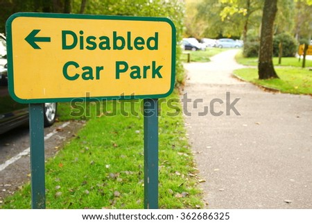 The disabled traffic signage at the car park background represent the sign and symbol concept related idea.