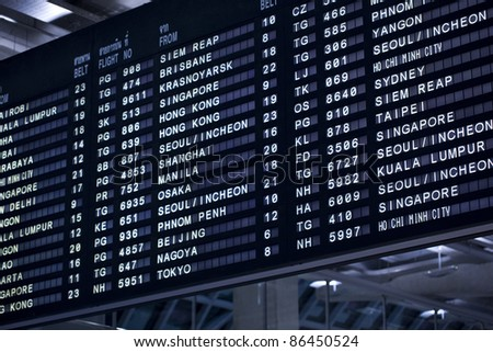 The display board in an airport with departure and arrival times. - stock photo