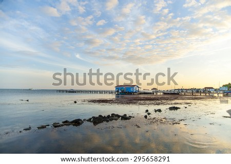 The distant pier lies in the still waters at San Pedro Belize on Ambergris Caye in Belize under a low-lying sunset and light cumulus clouds - stock photo