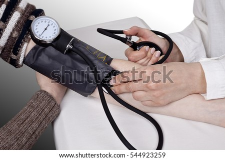 The doctor measures blood pressure in the patient