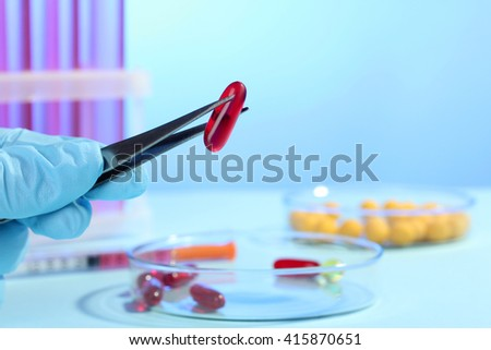 the doctor pulls the pill with tweezers from the Petri bowl on a wooden table