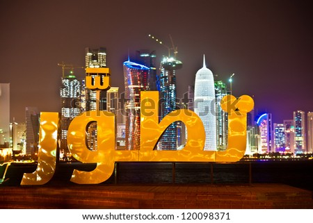 The Doha corniche at night time with Arabic wording in the foreground.