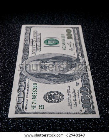 The 100 dollars greenback lie on dark surface in vertical perspective - stock photo