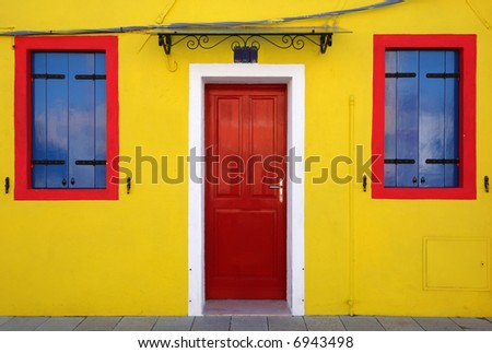 The door and two windows of a bright yellow house in perfect symmetry. Taken on the island of Burano near Venice, Italy. - stock photo