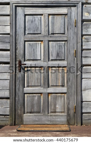 The door in the old rural house is made of the non painted  grown weathered  old pine and fir-tree boards