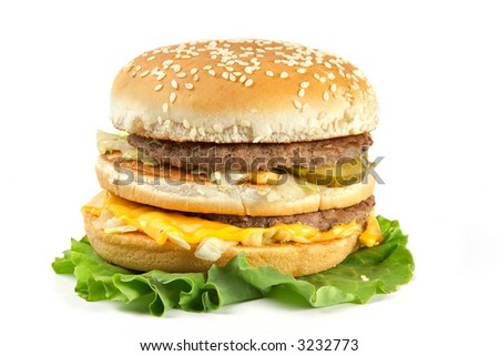 The double hamburger lays on leaves of lettuce, isolated on white background
