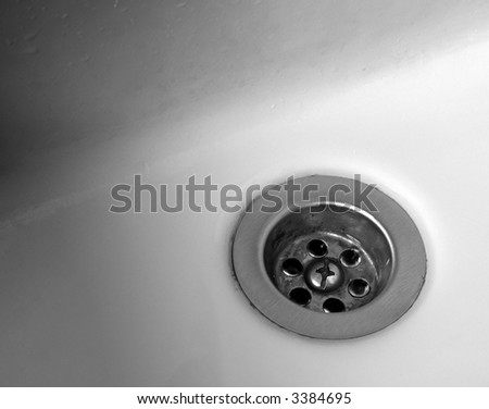 The drain of a porcelain bathroom sink in grayscale.