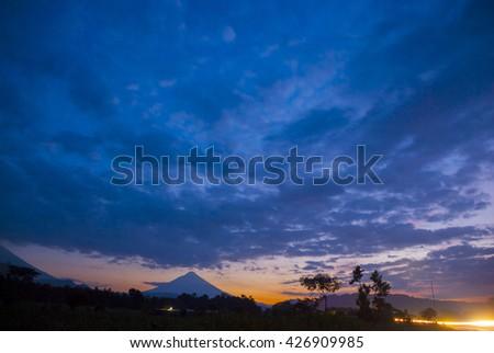 The dramatic evening sun on the roadand volcano in Guatemala - stock photo