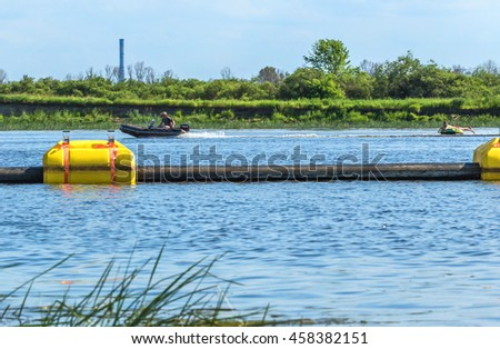 The dredger sucks in the river sand and gravel from the bottom of the river and transports it through a floating with orange floats ashore. The boat carries an inflatable human circle - stock photo
