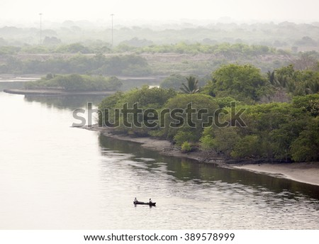 The drifting boat with two men in calm waters at dawn (Puerto Chiapas, Mexico). - stock photo