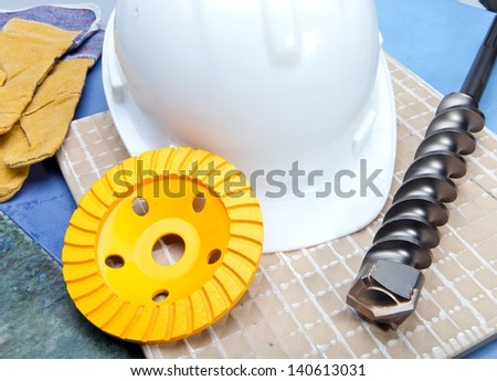 The drill, grinding disk for operation on concrete, a helmet protective and gloves working - stock photo