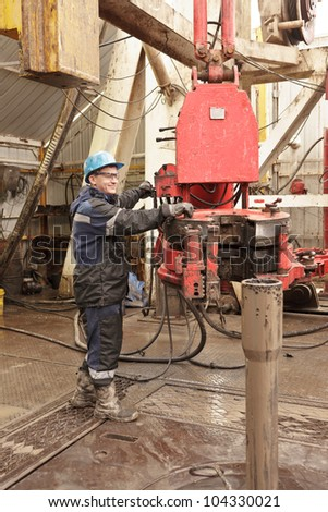 The driller operates the tool on workplace - stock photo
