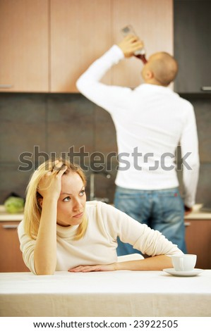 The drinking husband and the upset wife on kitchen - stock photo