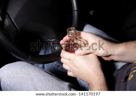 The driver drinking alcohol in the car