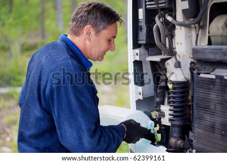 The driver filling a liquid to the motor - stock photo