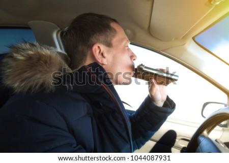 The driver of an alcoholic drinks cognac while driving a car. A man of 50 years is driving a car and drinking alcohol from a flask.