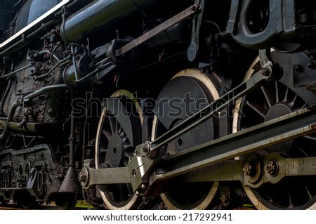 The driving wheels of a steam locomotive as it passes close at hand on the tracks - stock photo