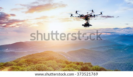 The drone with the professional camera takes pictures of the misty mountains at sunset - stock photo