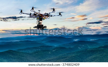 The drone with the professional cinema camera flying over the misty mountains at sunset.  - stock photo